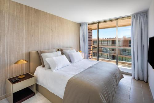 A bed or beds in a room at the Quest - Luxury Beach Apartment