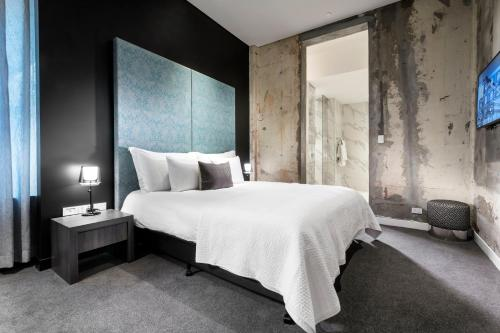 A bed or beds in a room at The Melbourne Hotel