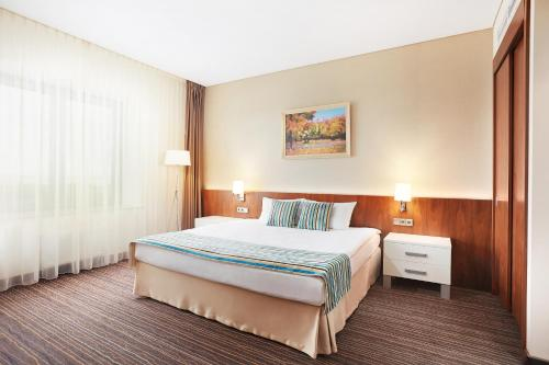 A bed or beds in a room at Victoria & SPA Minsk