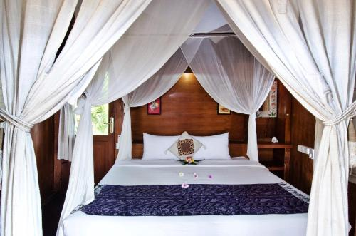A bed or beds in a room at Lumbung Bali Huts