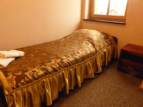 A bed or beds in a room at Karczma Góralska