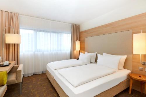 Ein Bett oder Betten in einem Zimmer der Unterkunft H+ Hotel Salzburg