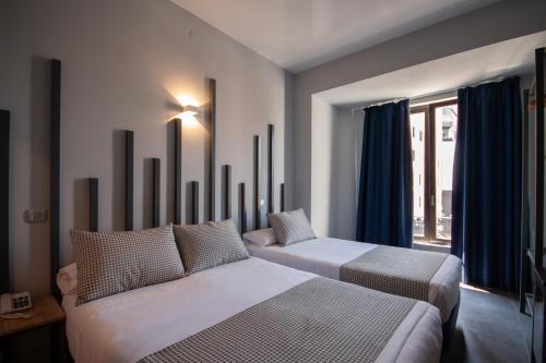 Un ou plusieurs lits dans un hébergement de l'établissement Hostal Carmen & Coworking