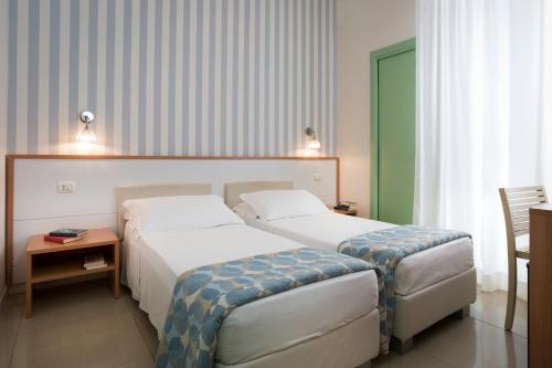 A bed or beds in a room at Hotel Calypso- Rimini Marina Centro