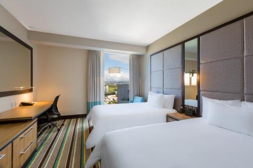 A bed or beds in a room at Hilton Garden Inn San Jose La Sabana, Costa Rica