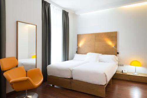 A bed or beds in a room at Petit Palace Plaza Málaga
