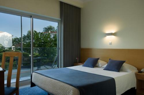 Uma cama ou camas num quarto em Cova da Iria Hotel