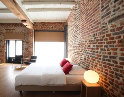 A bed or beds in a room at Hotel The Lodge Heverlee