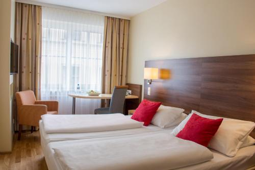 A bed or beds in a room at Hotel Alpha Wien