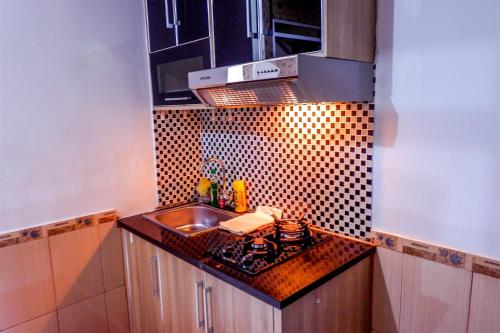 A kitchen or kitchenette at Strategic 2BR Menteng Square Apartment By Travelio