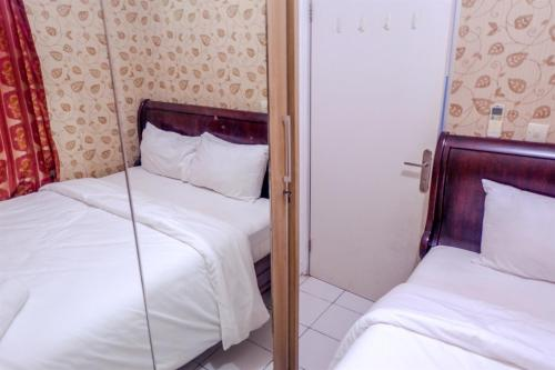 A bed or beds in a room at Strategic 2BR Menteng Square Apartment By Travelio