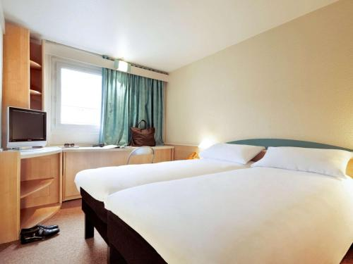 A bed or beds in a room at ibis Berlin City West