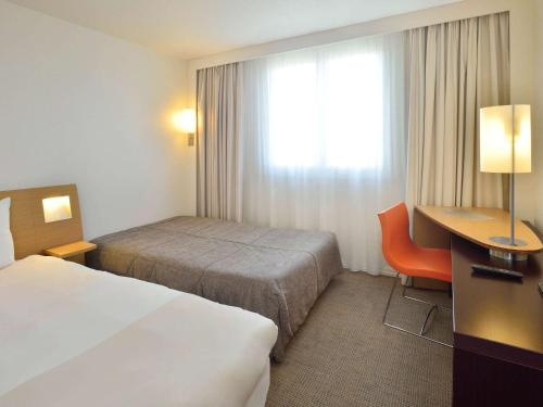 A bed or beds in a room at Novotel Bayeux