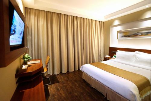 A bed or beds in a room at Maixinge Boutique Hotel Chuansha Branch