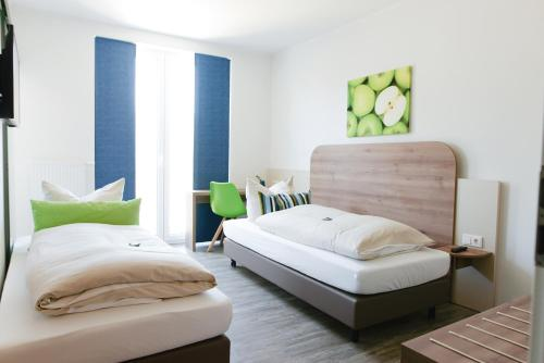 A bed or beds in a room at Hotel M24 - Alle Zimmer mit Küchenzeile