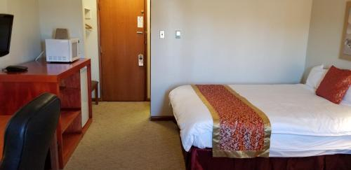 A bed or beds in a room at Redwood Motor Inn