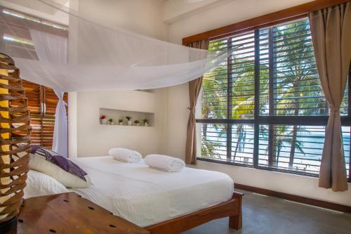 A bed or beds in a room at Makao Beach Hotel