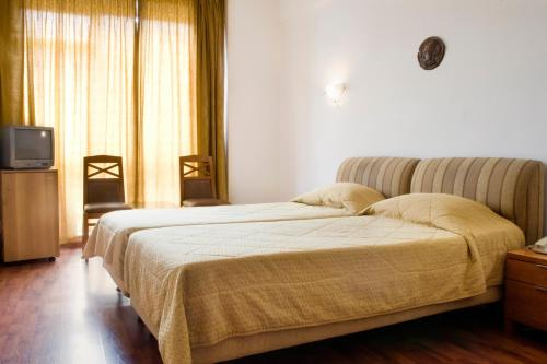 A bed or beds in a room at Arethusa Hotel