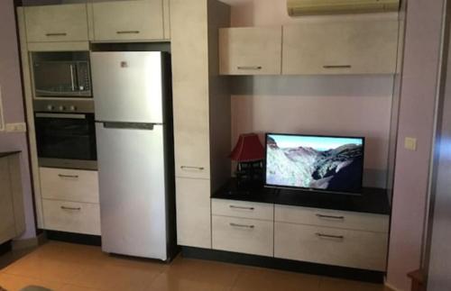 Uma TV ou centro de entretenimento em Bungalow Heipoe