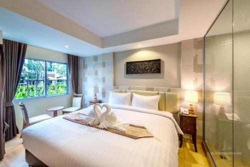 A bed or beds in a room at Suvarnabhumi Ville Airport Hotel