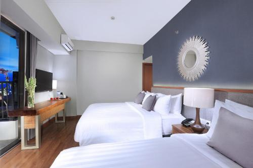 A bed or beds in a room at Aston Inn Batu