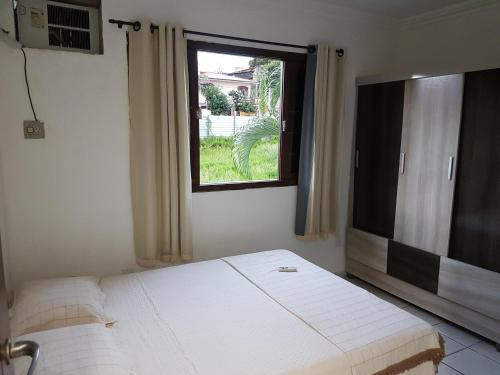 A bed or beds in a room at Casa em Ponta Negra