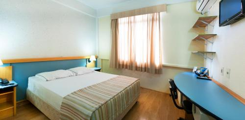 A bed or beds in a room at Brivali Hotel Centro