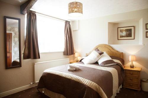 A bed or beds in a room at The Fat Lamb Country Inn and Nature Reserve