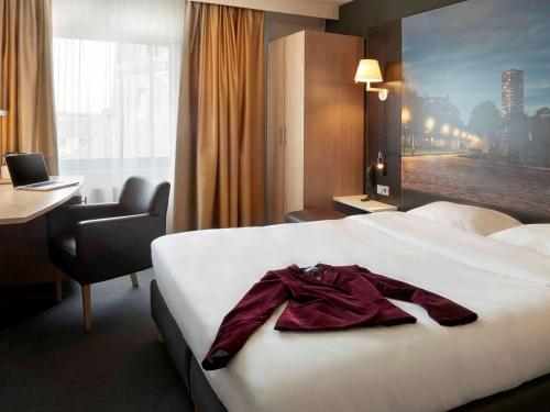 A bed or beds in a room at Mercure Hotel Tilburg Centrum