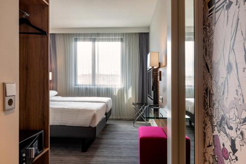 A bed or beds in a room at Moxy Munich Airport
