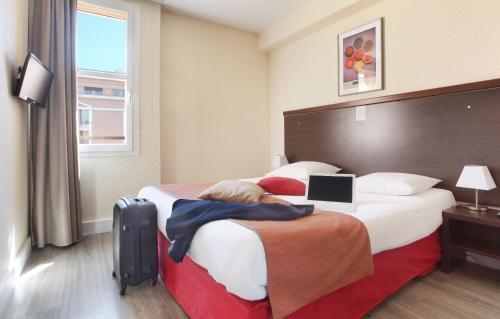 A bed or beds in a room at Odalys City Aix en Provence L'Atrium
