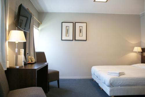 A bed or beds in a room at Fletcher Hotel Restaurant Bon Repos