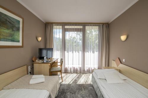 A bed or beds in a room at Geovita Zakopane