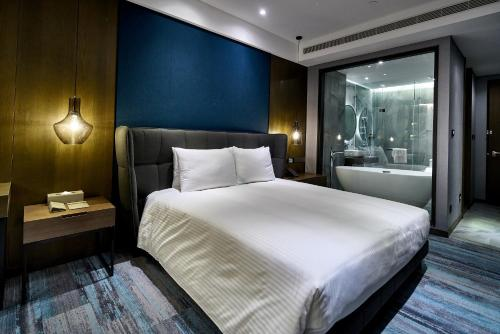 A bed or beds in a room at Harbour 10 Hotel