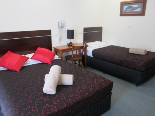 A bed or beds in a room at Snowgum Motel