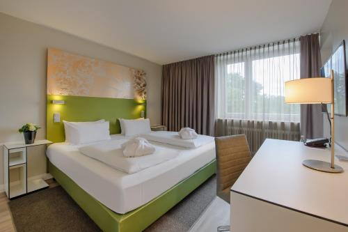 A bed or beds in a room at Congress Hotel Mercure Nürnberg an der Messe