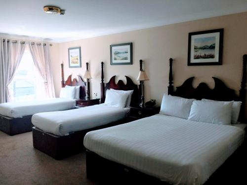 A bed or beds in a room at Shamrock Inn Hotel