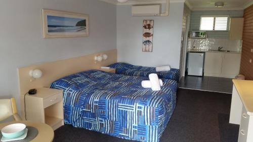 A bed or beds in a room at Dolphins of Mollymook Motel and Fifth Green Apartments