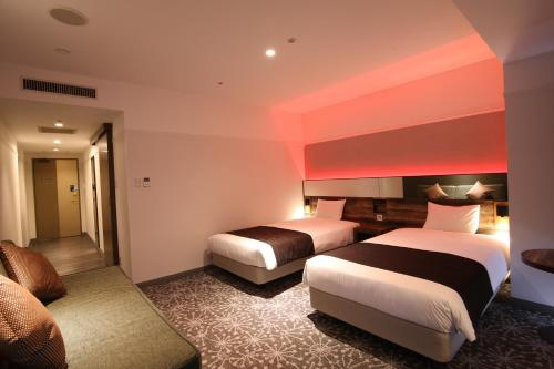 A bed or beds in a room at Quintessa Hotel Sapporo