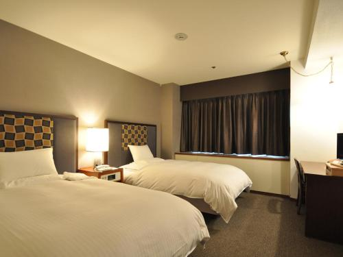 A bed or beds in a room at Mito Keisei Hotel