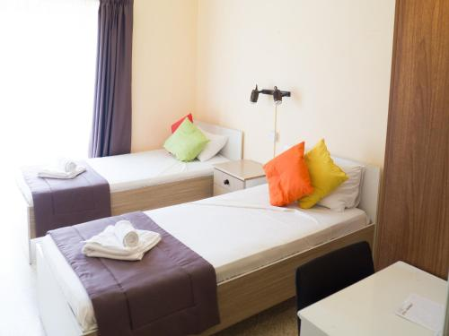 A bed or beds in a room at Mavina Hotel & Apartments