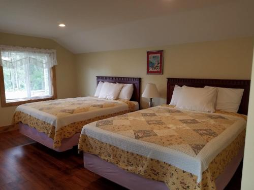 A bed or beds in a room at Grand View Motel and Cottages