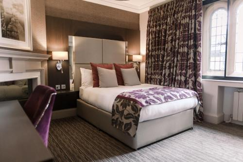 A bed or beds in a room at Abbey House Hotel