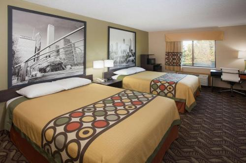 A bed or beds in a room at Super 8 by Wyndham Dwight