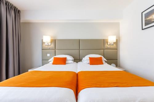 A bed or beds in a room at Hotel Nice Riviera