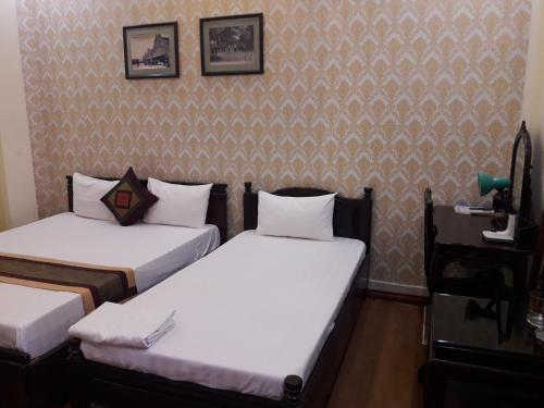 A bed or beds in a room at Hanoi City Guest House