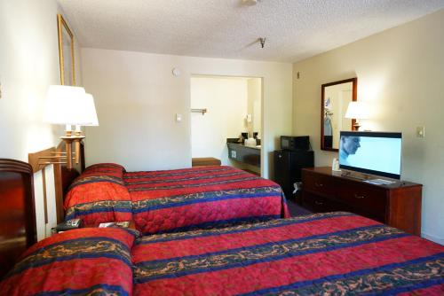 A bed or beds in a room at Ambassador Inn Fresno