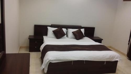سرير أو أسرّة في غرفة في أجنحة القمة للشقق المفروشة