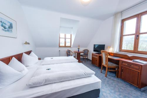 A bed or beds in a room at Landhotel Rhönblick