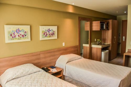 A bed or beds in a room at Mont Blanc Suites Duque de Caxias